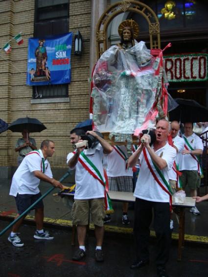"Stephen LaRocca (right) shouts: ""Viva Saint Rocco"" (Long live Saint Rocco) as the men dutifully carry their Patron despite the elements"