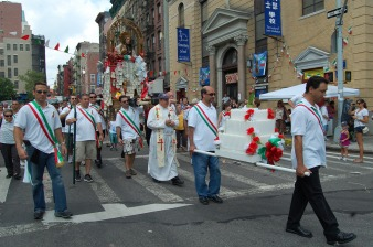 """The Chaplain and members of The Saint Rocco Society of Potenza carry """"U Cinte"""" (candelabra) past the old Saint Joseph Church in the old Fourth Ward"""